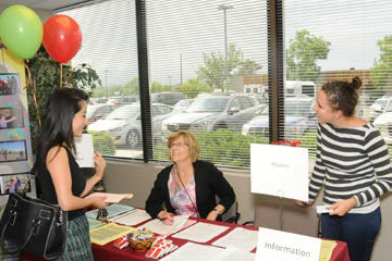 People talking around a demonstration table at an old Provider Fair